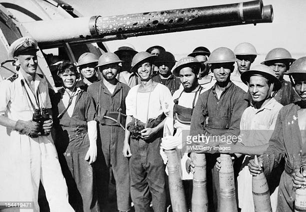 Indian Naval Forces In Burma Lieutenant M H Jerram RINVR with the gun crew of the Indian sloop NARBADA at Myebon Burma The gun barrels were blistered...