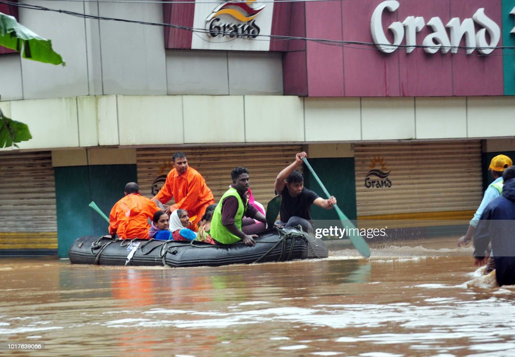 Indian navy and rescue personnel evacuate local residents in an boat at Aluva, in the Indian state of Kerala, on August 16, 2018. - The death toll from floods in India's tourist hotspot of Kerala increased to 77 on August 16, as torrential rainfall threatened new areas, officials told AFP.