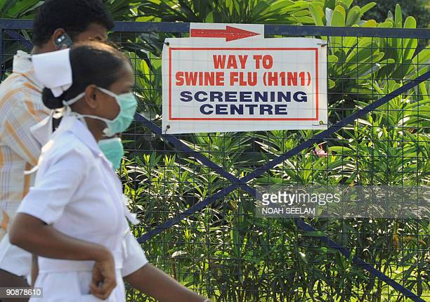 Indian nurses and patients walk towards the swine flu screening centre at the Government Gandhi Hospital in Hyderabad on September 17 2009 More than...