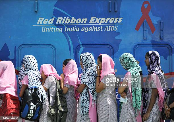 Indian nursing trainee students stand in a line to enter the Red Ribbon ExpressIII train car during an HIV/AIDS awareness campaign at a railway...