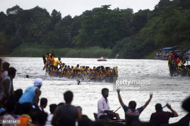 Indian oarsmen row a serpentine boat as they compete in the Mahatma boat race along the Pamba river ahead of Onam celebrations in Chengannur near the...