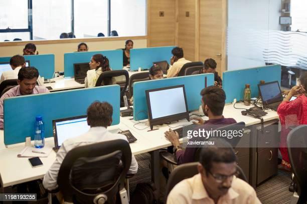 自分のコンピュータの前に座っているインドのサラリーマン - 南アジア ストックフォトと画像