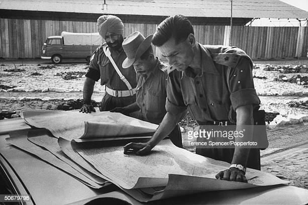 Indian officers with Gurkha Troops arriving in Leo'ville studying maps of the area
