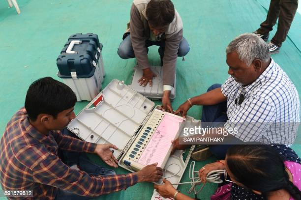 Indian officials check an Electronic Voting Machine ahead of the 2nd phase of Gujarat Vidhan Sabha elections in Ahmedabad on December 13 2017 Gujarat...