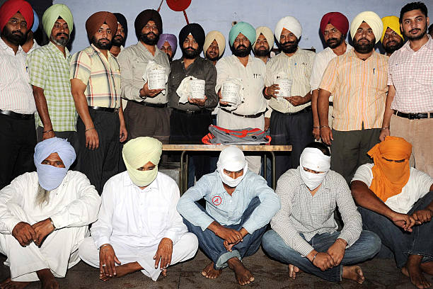 Indian officials from the special narcotics cell of the Punjab state police force pose with sacks containing heroin as they display suspected...