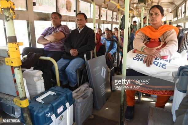 Indian officials travel on a bus with Electronic Voting Machines and Voter Verifiable Paper Audit Trail ahead of the 2nd phase of Gujarat Vidhan...