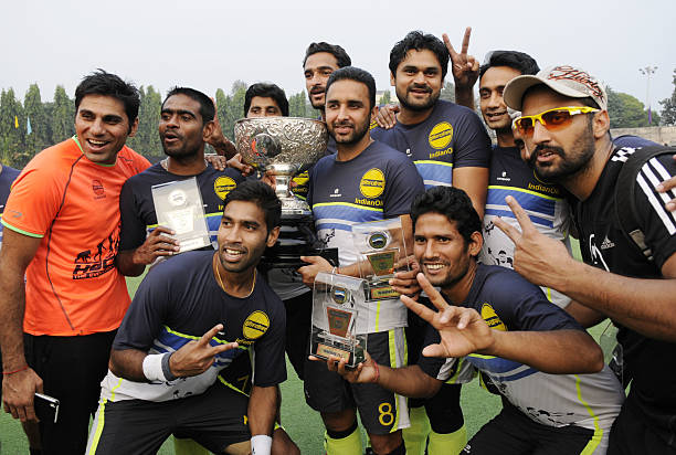 Indian Oil Corporation player cheers and flash victory sign as they receive winners trophy from Keshari Nath Tripathi after defeating Punjab National.