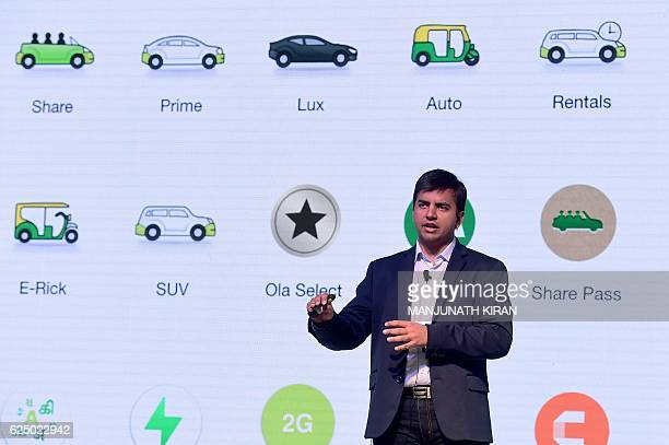 Indian Ola app co-founder and CEO Bhavish Aggarwal gestures as he addresses a press conference in Bangalore on November 22, 2016. Ola has announced...