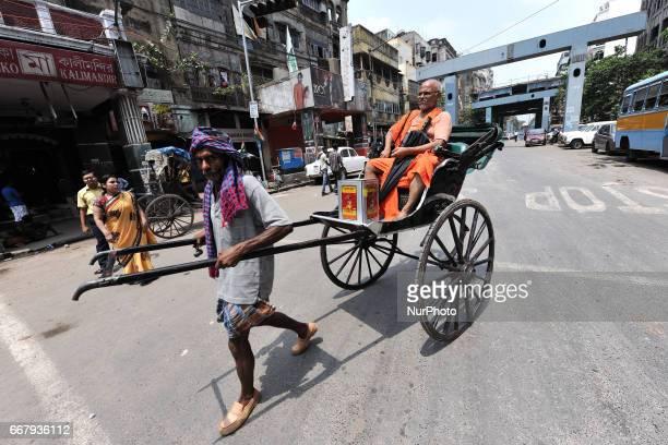 Indian Old man pulling hand rickshaw with passengers iN North KolkataIndia on April 12 2017