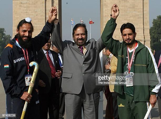 Indian Olympic Association President Suresh Kalmadi raises his hands with India hockey captain Rajpal Singh and Pakistan hockey captain Zeeshan...