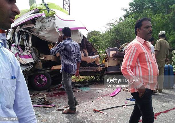 Indian onlookers stand next to the wreckage of a minibus in which a group of Spanish tourist were travelling after it collided with a container truck...