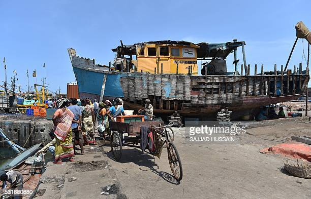 Indian onlookers stand on the edge of a dock at a fishing harbour in Visakhapatnam on May 16 2016 The government of Andhra Pradesh has imposed a...