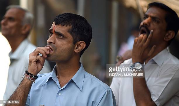 Indian onlookers watch share prices on a digital broadcast on the facade of the Bombay Stock Exchange in Mumbai on January 6 2015 The BSE 30 share...