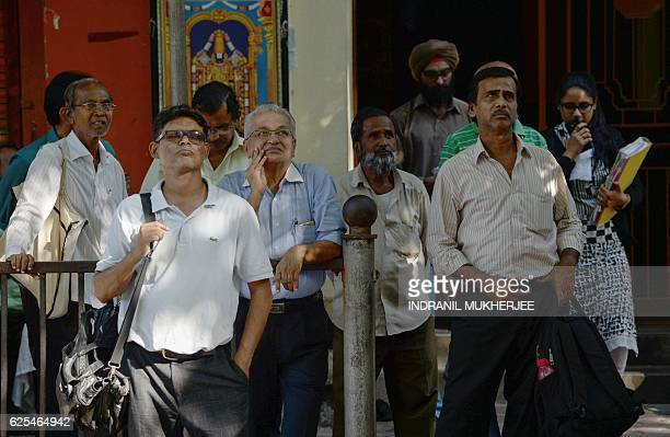 Indian onlookers watch share prices on a digital brodcast on the facade of the Bombay Stock Exchange during intraday trade in Mumbai on November 24...