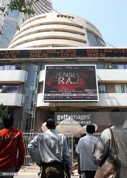 Indian onlookers watch the Bombay Stock Exchange digital broadcast outside the BSE in Mumbai on October 24 2008 Indian shares plunged more than 10...