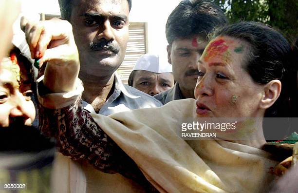 Indian Opposition leader and Congress Party President Sonia Gandhi places a dot of coloured powder on a supporters forehead as she sports coloured...