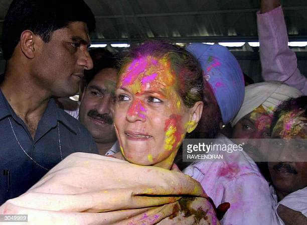 Indian Opposition leader and Congress Party President Sonia Gandhi is greeted by her supporters as she wears a garland and coloured powder on her...