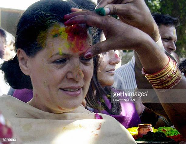 Indian Opposition leader and Congress Party President Sonia Gandhi has coloured powder applied to her forehead during celebrations for 'Holi' at her...