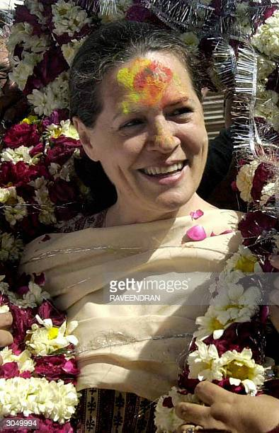 Indian Opposition leader and Congress Party President Sonia Gandhi smiles as she wears a garland and coloured powder on her forehead during...