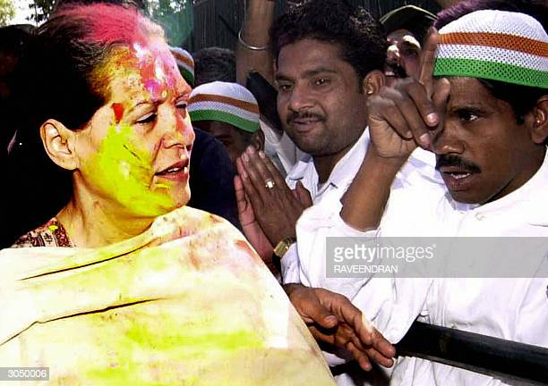 Indian Opposition leader and Congress Party President Sonia Gandhi sports coloured powder marks on her forehead as she is greeted by supporters...