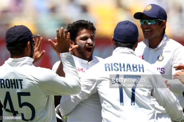 Indian paceman Shardul Thakur celebrates his wicket of Australia's batsman Marcus Harris with teammates on day one of the fourth cricket Test match...
