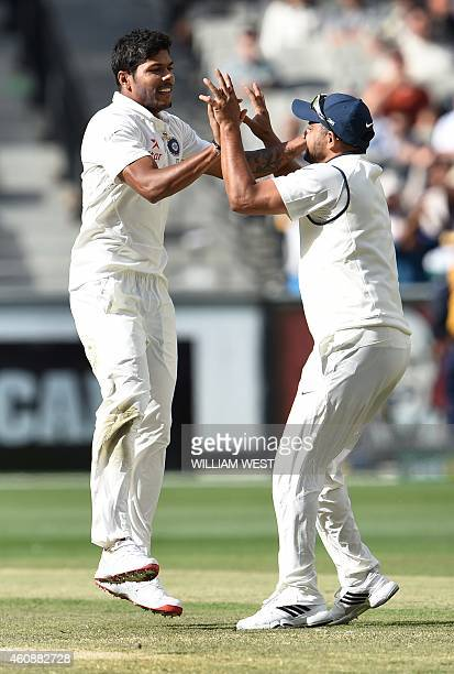 Indian paceman Umesh Yadav is congratulated by teammate Suresh Raina after dismissing Australian batsman Brad Haddin on the fourth day of the third...