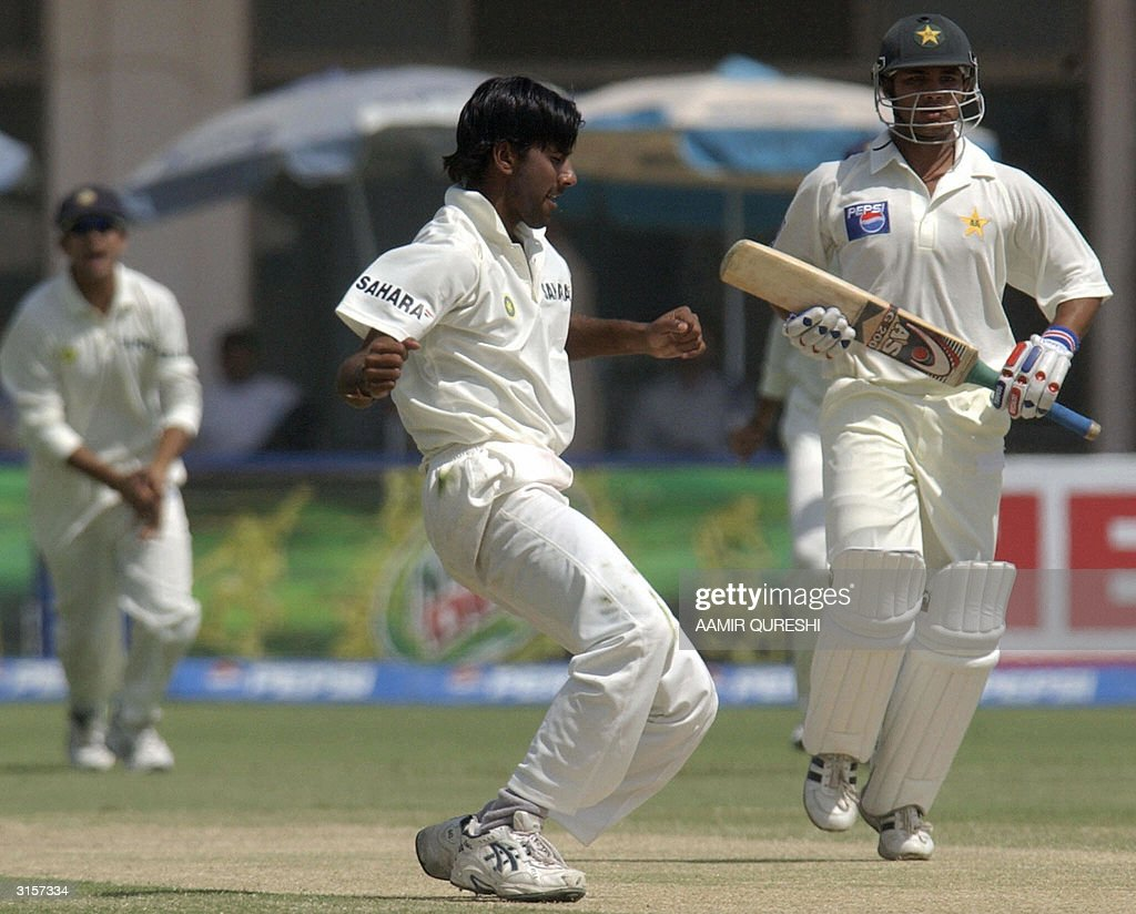 Indian pacer Laxmipathy Balaji (C) celebrates his wicket as Pakisani opener Imran Farhat (R) passes by on the third day of the first test match between Pakistan and India in Multan, 30 March 2004. Indian pacers grabbed two Pakistani wickets as Pakistan still need 339. AFP PHOTO/Aamir QURESHI