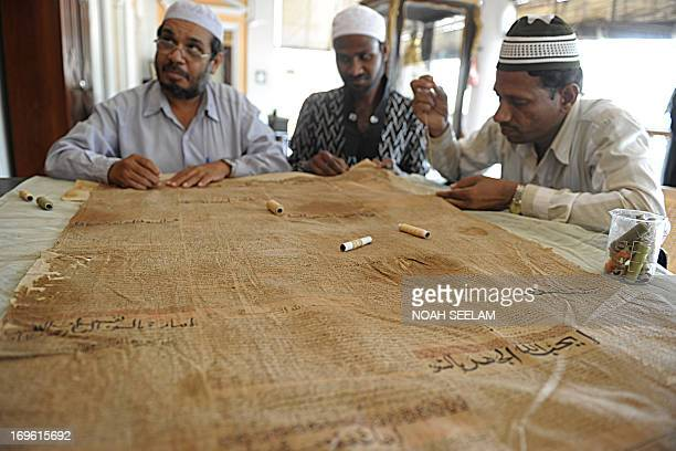 Indian paper conservators restore an antique Islamic document at Chowmahalla Palace in Hyderabad on May 29 2013 Some 300 antique copies of the Koran...