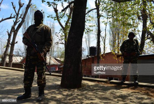 Indian Paramilitary force personals stand guard outside a polling station in central kashmir's Budgam district during ByPolls of Indian Parliamentary...
