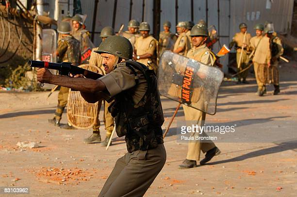Indian paramilitary forces aim after rock throwing protesters as tensions on the streets erupt in to clashes after Friday prayers on October 3 2008...