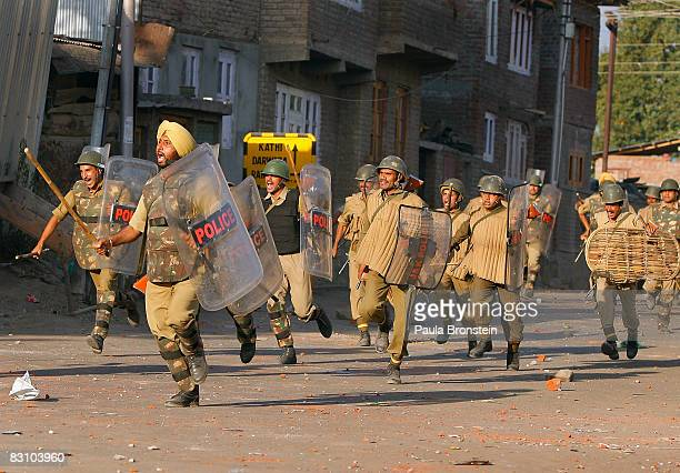 Indian paramilitary forces run after rock throwing protesters as tensions on the streets erupt in to clashes after Friday prayers on October 3 2008...