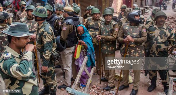 Indian paramilitary forces shield a Hindu woman in the majority community in a riot- affected area on February 28, 2020 in New Delhi, India. At least...