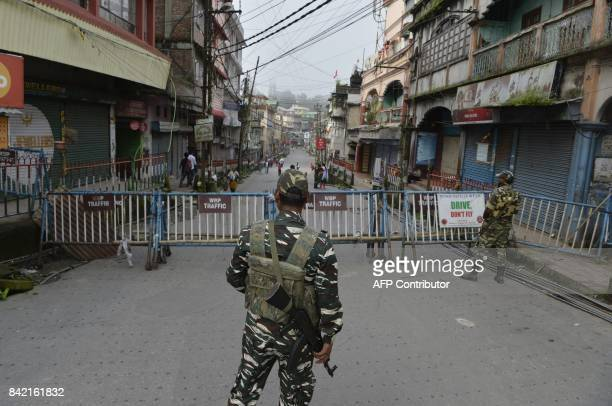 Indian paramilitary forces stand guard at the main market area during the 83th day of an indefinite strike called by the Gorkha Janmukti Morcha for...