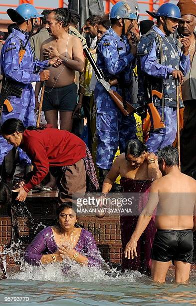 Indian paramilitary officials walk past as Hindu devotees offer prayers after the solar eclipse on the banks of the river Ganges in Haridwar on...