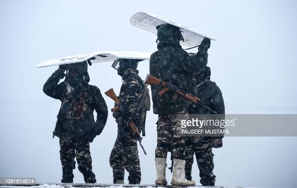 Indian paramilitary personnel stand guard on the shore of the Dal lake during a heavy snowfall in Srinagar on January 31, 2019. - Security has been...