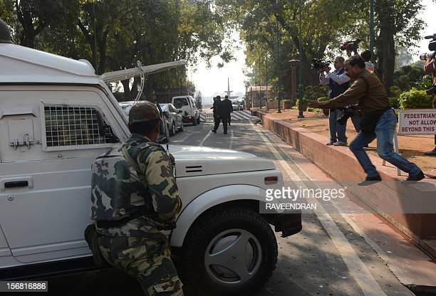 Indian paramilitary security commandos take precautionary positions following a car alarm that went off on the premises of the Parliament House...