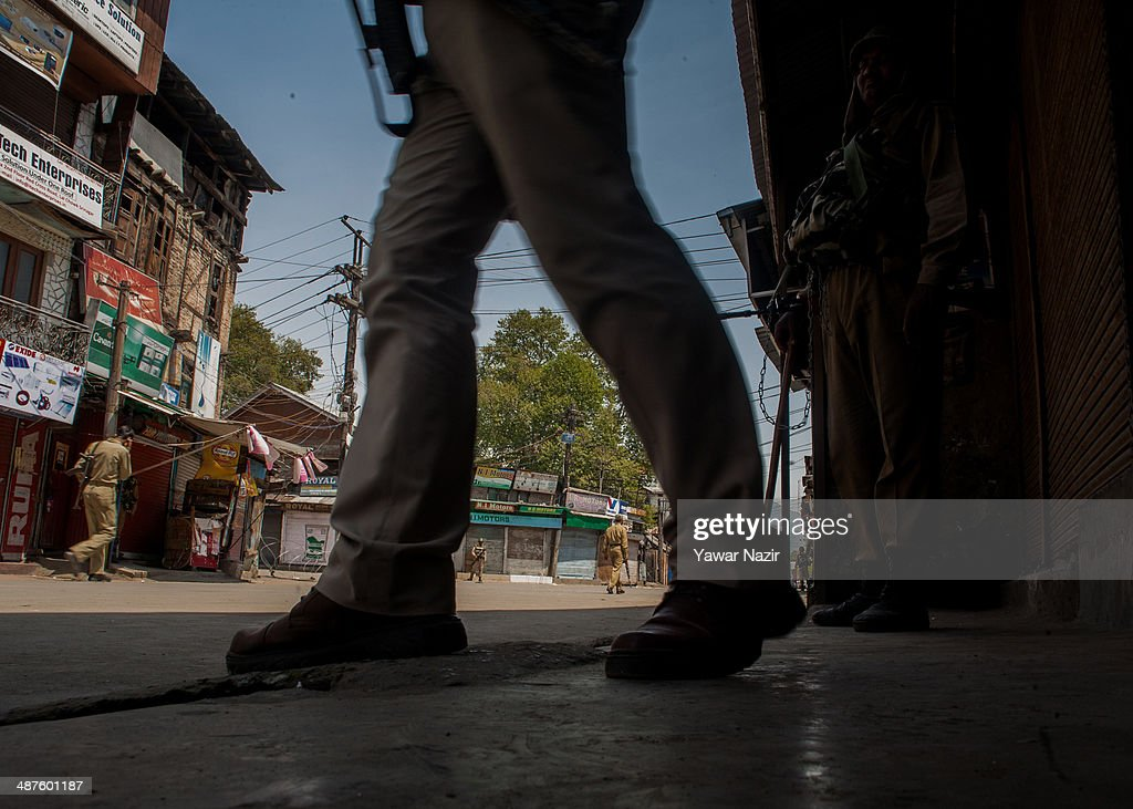 Indian paramilitary soldier guard the deserted roads in the main city during a curfew following a killing of a youth on May 01, 2014 in Srinagar, the summer capital of Indian-administered Kashmir, India. Kashmir remained on boil a day after a youth was shot dead by Indian armed government forces in the Old City of Srinagar. Two persons including a woman were also wounded when Indian forces fired at Kashmiri stone hurling protesters who were shouting 'down with India' slogans. The Indian forces in Kashmir clamped a stringent curfew in the region to stop anti-India protests from escalating while as a shutdown was observed to protest the killing of the youth.