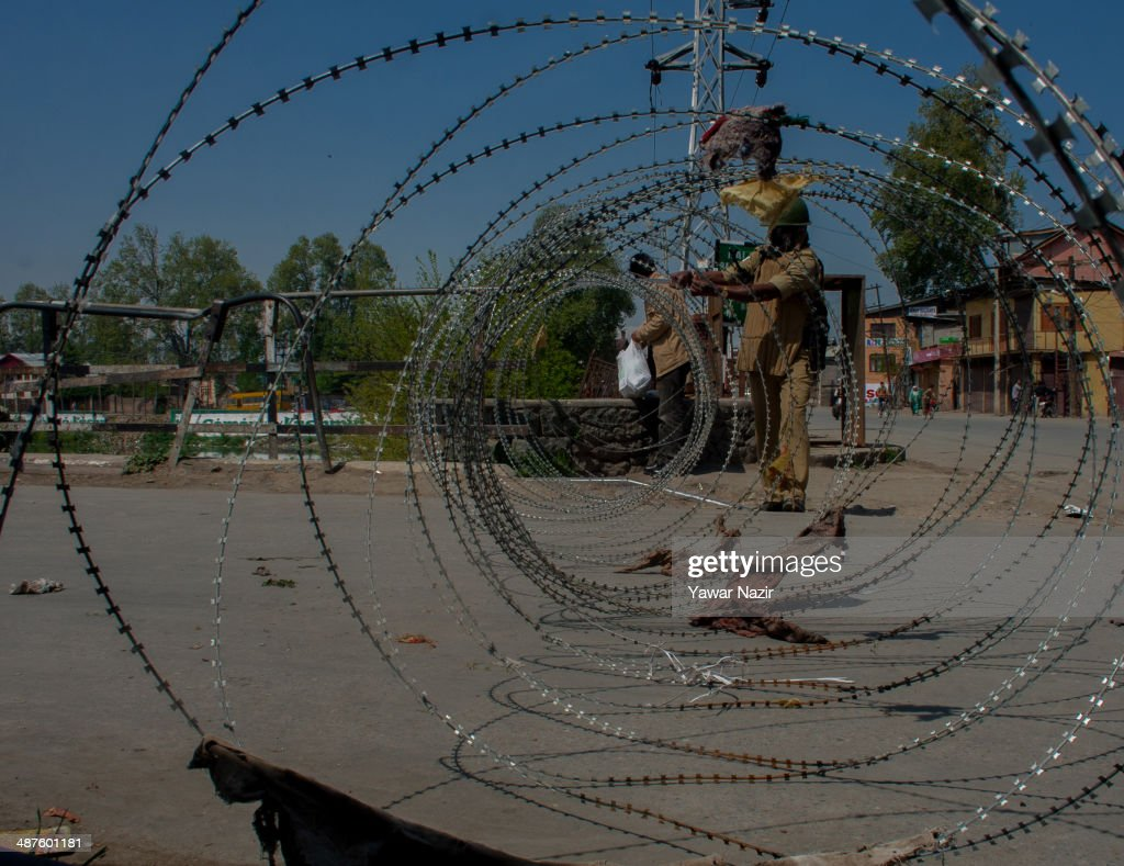 Indian paramilitary soldier maintains the concertina razor wire during a curfew following a killing of a youth on May 01, 2014 in Srinagar, the summer capital of Indian-administered Kashmir, India. Kashmir remained on boil a day after a youth was shot dead by Indian armed government forces in the Old City of Srinagar. Two persons including a woman were also wounded when Indian forces fired at Kashmiri stone hurling protesters who were shouting 'down with India' slogans. The Indian forces in Kashmir clamped a stringent curfew in the region to stop anti-India protests from escalating while as a shutdown was observed to protest the killing of the youth.