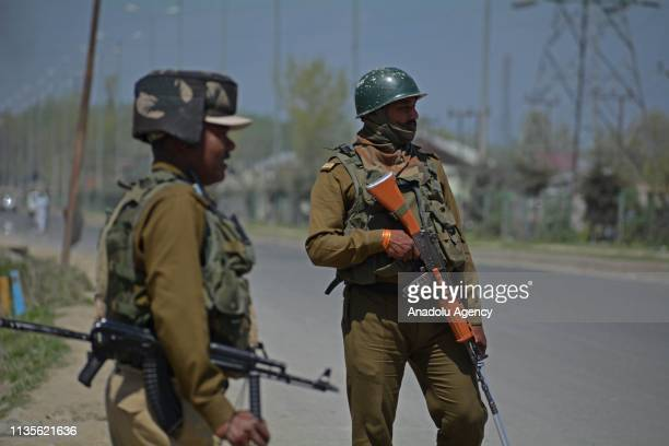 Indian paramilitary soldiers guard the national highway as an Indian Army convoy crosses on the outskirts of Srinagar Kashmir on April 07 2019 Indian...