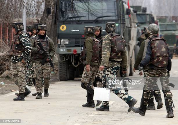 Indian paramilitary soldiers make their way to the encounter site where nine people including four Indian army men three militants a policeman and a...