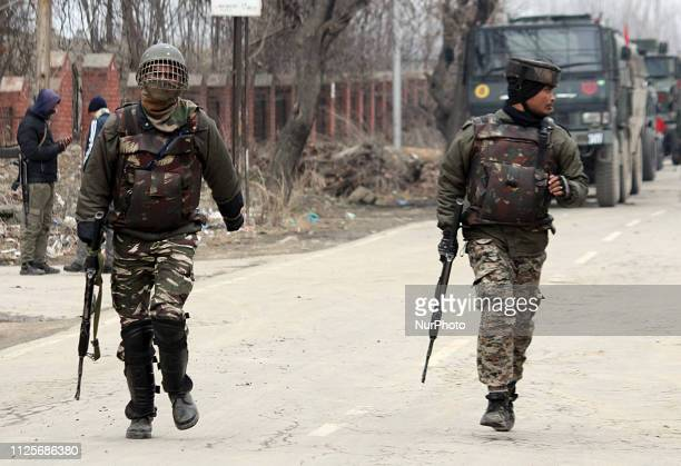 Indian paramilitary soldiers run near the encounter site in Pinglena area of Pulwama some 30 kilometers from Srinagar Kashmir on February 18 2019Nine...
