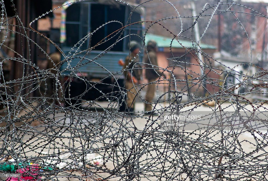 Indian paramilitary soldiers stand guard in front the concertina razor wire during a strict curfew on the seventh consecutive day, imposed after the execution of alleged Indian parliament attacker Mohammad Afzal Guru on February 15, 2013 in Srinagar, the summer capital of Indian Administered Kashmir, India. Afzal Guru, from Sopore town in the north of Kashmir, was hung on February 09 for his role in the 2001 Indian parliament attack which left 14 dead. The hanging has further strained relations between India - who blamed the attack on 'Pakistan backed' militant group Jaish-e-Mohammed - and neighbouring Pakistan and has seen an military increase from both along the border.Curfew was lifted from some parts of Srinagar after four days.