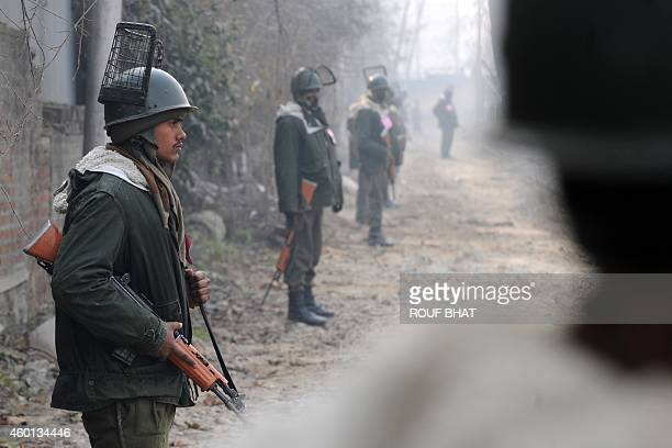 Indian paramilitary soldiers stand guard on a deserted street during a curfew in Srinagar on December 8 2014 Prime Minister Narendra Modi is set to...