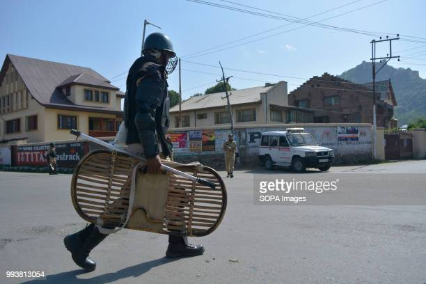 Indian paramilitary trooper patrols the deserted streets during curfew restrictions on the second death anniversary of Burhan Muzaffar Wani a young...