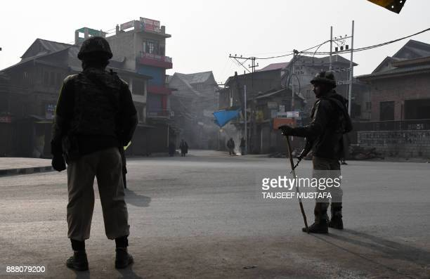 Indian paramilitary trooper stands guard near Jamia Masjid mosque during a restriction in Srinagar on December 8 2017 A partial restrictions have...
