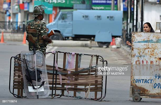 Indian paramilitary trooper stops a Kashmiri pedestrian during a curfew in Srinagar on August 18 2016 More than 60 civilians have been killed in...