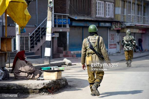 Indian paramilitary troopers seen patrolling next to a road side vendor during restrictions in Srinagar Authorities imposed restrictions in parts of...
