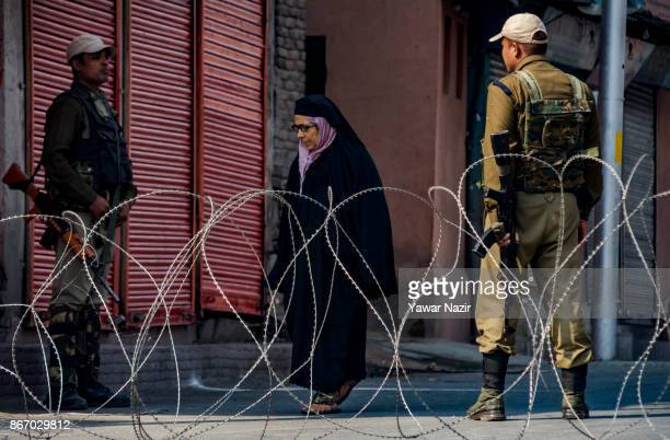 Indian paramilitary troopers stand alert as a Kashmiri Muslim woman walks on a deserted road during a strike on October 27 2017 in Srinagar the...