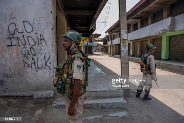 Indian paramilitary troopers stand alert in front the shuttered shops during a strike restrictions on the third death anniversary of Burhan Wani on...