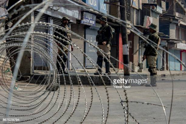 Indian paramilitary troopers stand alert on a deserted road during a strike on October 27 2017 in Srinagar the summer capital of Indian administered...